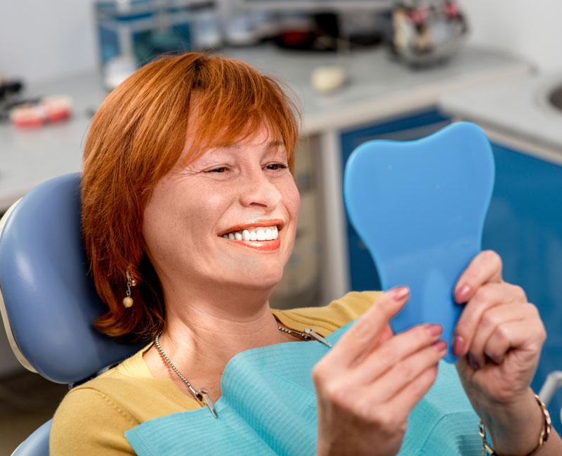 women inspecting new dentures
